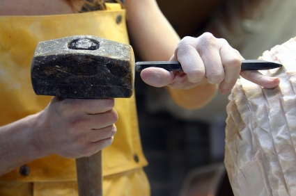 A sculptor shapes marble with a chisel.